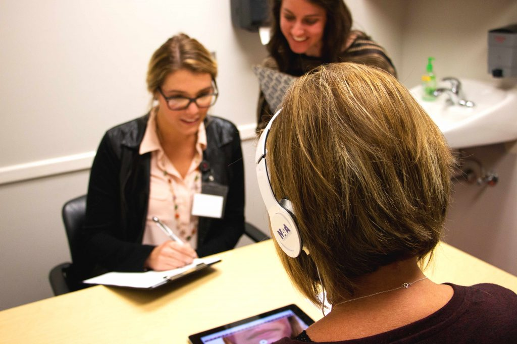 two therapists use an iPad to evaluate a client