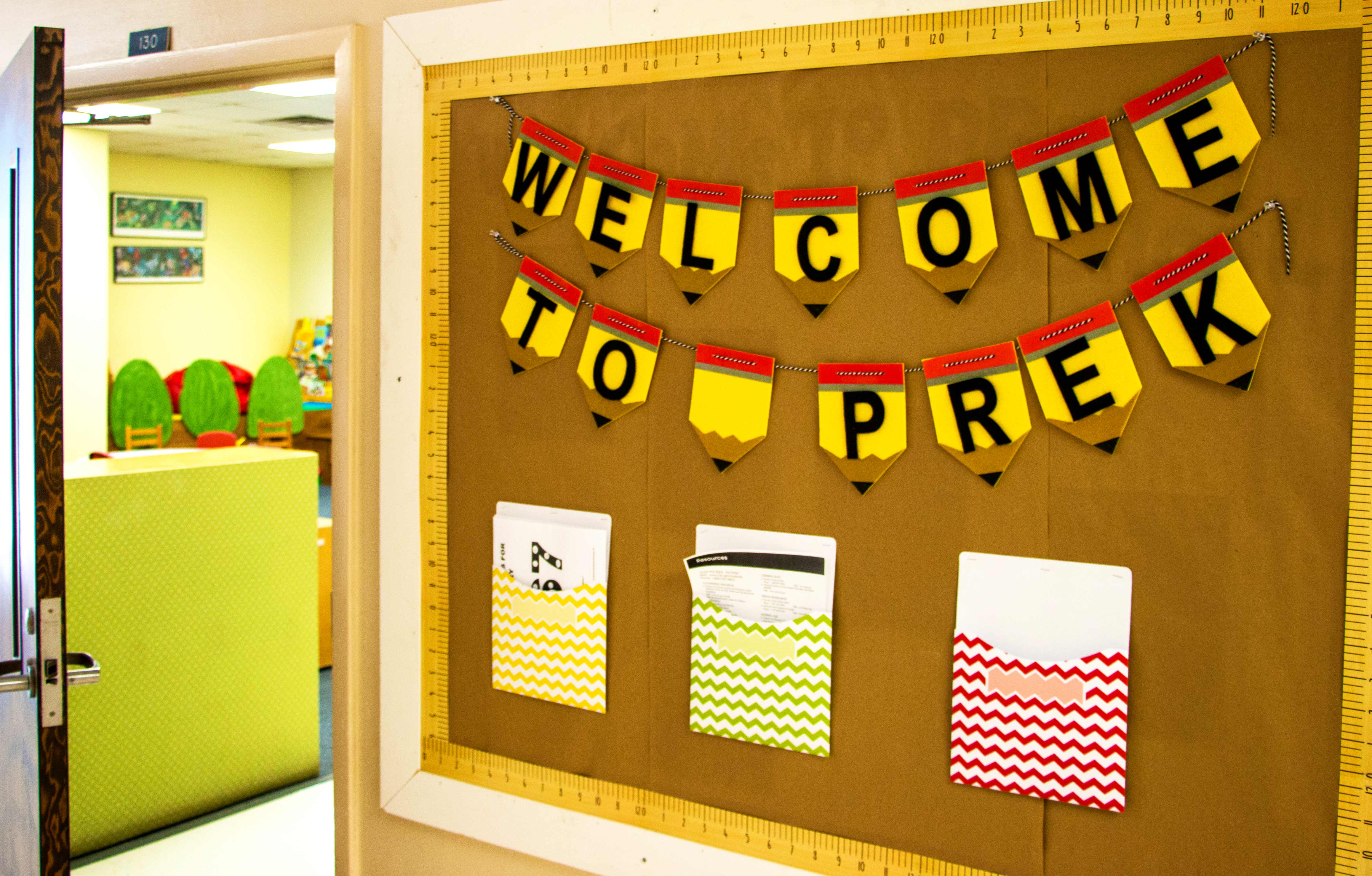 "a bulletin board with ""Welcome to Pre-K"" in block letters"