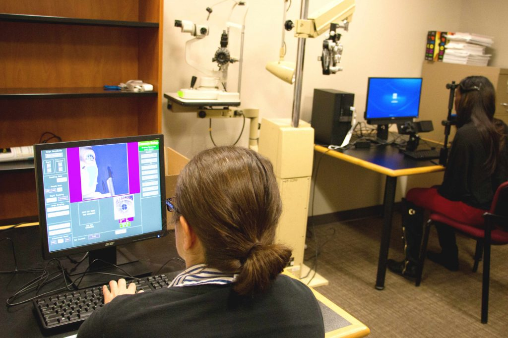 a woman looks at a computer monitor on which appears the image of another woman's face; the second woman is seated in front of a camera across the room